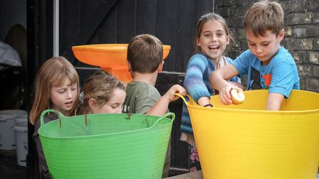 Children have a rummage through brightly coloured buckets for apples at The Railway Arms