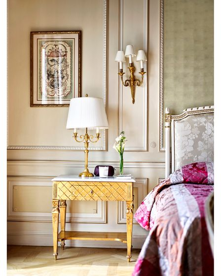 gold bedside table, painted panelling on the wall, green washed silk wallcovering behind the bed, silk jaquard headboard