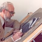 An artist, Kenneth Padley, at an easel painting a badger