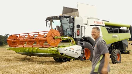 Andy Crow in front of his Claas combine harvester in a field of wheat
