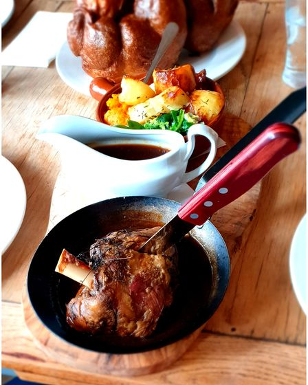 A large lamb shank in a pan, with a gravy boat, roast potatoes and brocolli