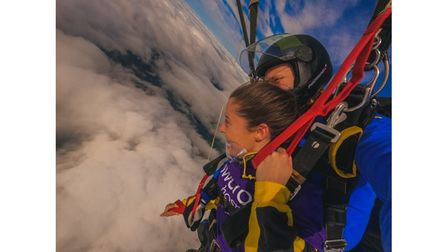 Skydiver and trainer in clouds