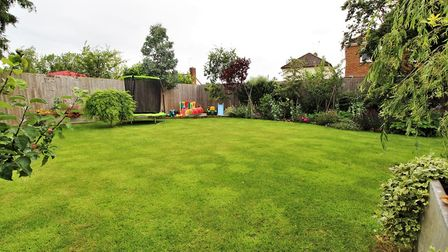 Beautifully verdant lawned garden enclosed by fencing, hedges and shrubs at the bungalow in Pudding Pie Close, Langford