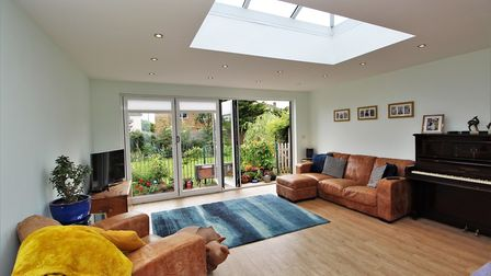 Modern white walled living area with wooden flooring, furniture and bi-folding doors with garden beyond.