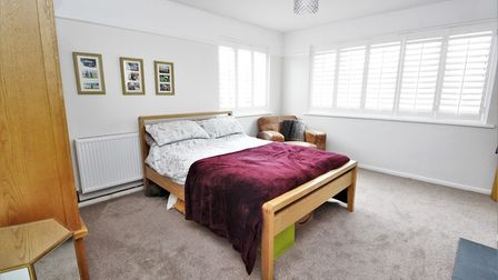 Double bedroom with oatmeal carpet, white walls, windows on two sides with white blinds and wooden furniture.