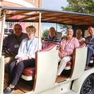 Passengers seated in an old vintage car