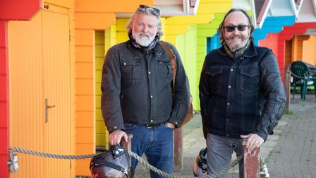The Hairy Bikers stand outside bright, colourful beach huts on a beach in Scarborough