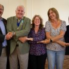 Five people linking hands and smiling at the camera