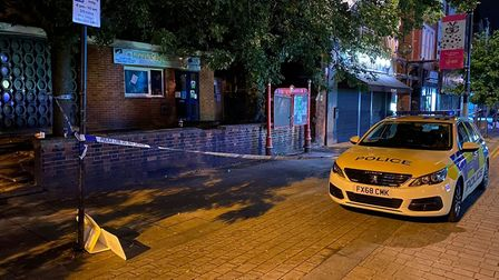 Police at the scene of a stabbing in Harlesden where a man was knifed in the back