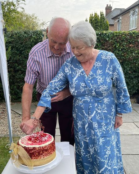 John and Jacqui Crouch cutting a cake on their anniversary