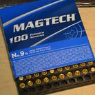 A box of Magtech primers on a wooden table