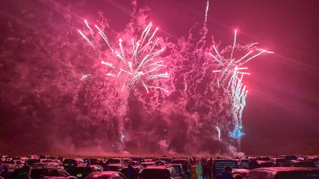 A group of cars watch the fireworks light up the night sky with pinks and reds