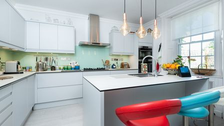 Modern contemporary kitchen with bright coloured stools in this 5-bed home for sale in Norwich