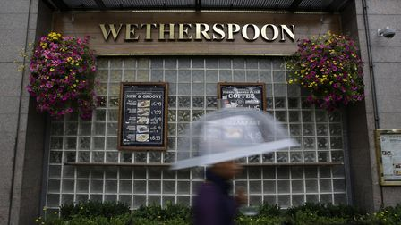 A pedestrian shelters from the rain beneath an umbrella as they walk past a JD Wetherspoon Plc pub i