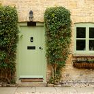 A front of a cottage with a green door and window.