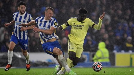 Brighton and Hove Albion's Dan Burn (centre) and Arsenal's Bukayo Saka battle for the ball during th