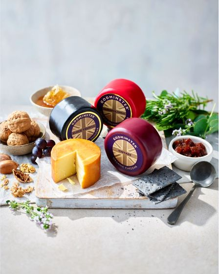 Three rounds of cheese are surrounded by sundries such as crackers.