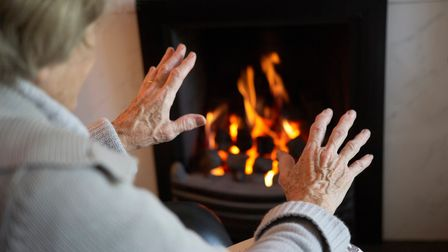old lady holding hands to a fire