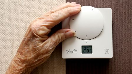 A generic stock photo of an elderly lady adjusting her thermostat on at home in Liverpool.