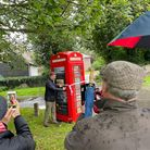 Tom Newcombe, chair of Great Chesterford Parish Council, cuts a ribbon on a red telephone box