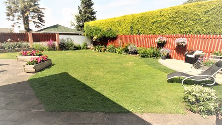 Lawned garden at the property in Valley Road, Portishead, with semi-circular patio and lounger and hedge and fence border.