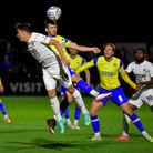 Dan Martin of Torquay United heads away from Kane Smith of Boreham Wood during the National League m