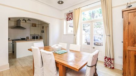 Dining room with wooden floor and furniture, white French doors and walls, with an archway to the kitchen.
