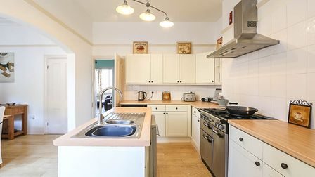 Kitchen in the house in Milton, Weston-super-Mare, with cream units, wooden worktops and an island with stainless steel sink.