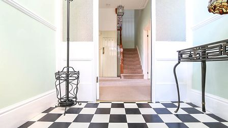 Entrance porch with chessboard flooring, mint walls, black metal table and coat and umbrella stand, with a door to the hall.