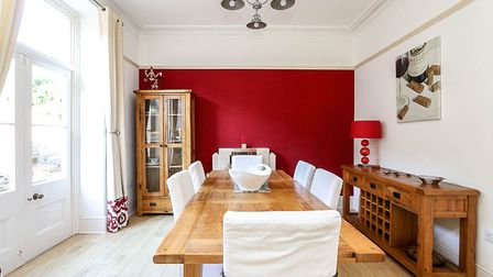 Dining room with wooden table, cream chairs, wooden sideboard, red far wall and white French doors overlooking the garden.
