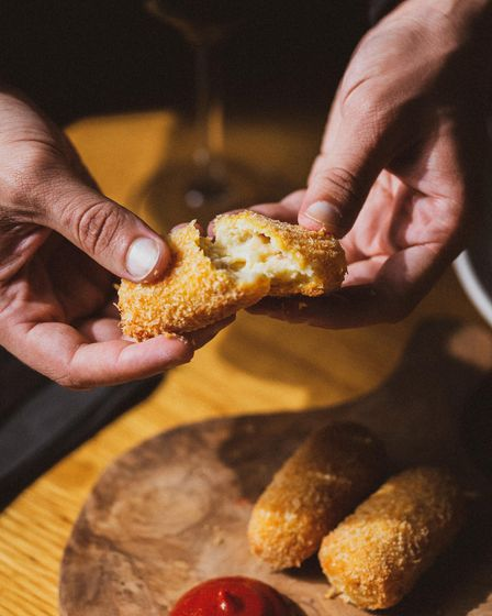 Croqueta being broken in half to show melting middle