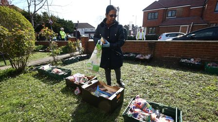 A local resident look at food packages in the front garden of James Giles' home in New Malden, south