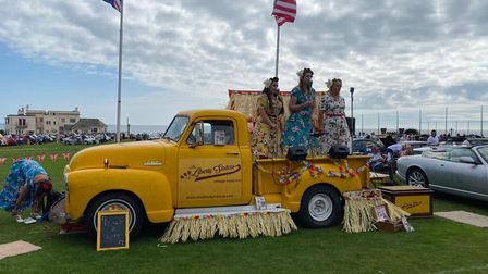 Three women singing on the back of a yellow vintage truck