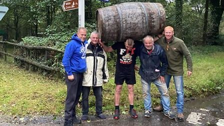 Five men pictured with the middle once carrying an oak barrel above his head
