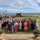 Guests at a 90th party gathered on a hotel front lawn with sea and blue sky behind.