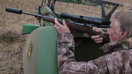 Mike Powell using a combine for cover while he shoots foxes with rifle