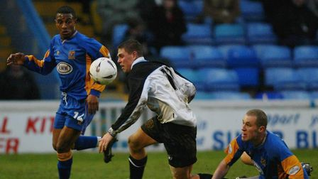 Barrow's Grant Holt (centre) attempting to break through the Shrewsbury defence of Leon Drysdale (lh
