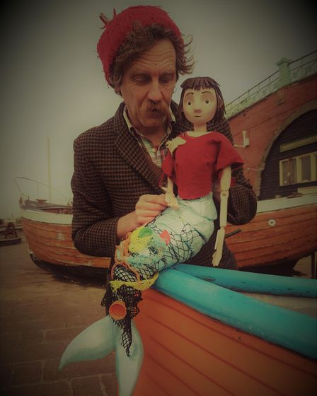 A man in a woolly hat holding a mermaid puppet sitting on a boat