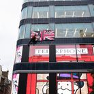Street artist Alec Monoploy abseils down the Flannels store on Oxford Street, London in celebration