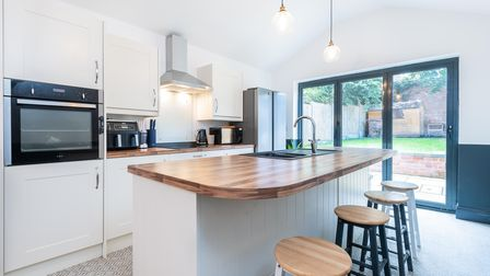 Modern fitted kitchen with kitchen island and patio doors outside in 3-bed terrace for sale on Alexandra Road, Norwich