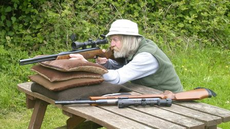 Jim Tyler shooting an air rifle bench rest, with another air rifle on the bench beside him