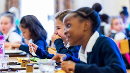 Schoolgirls eating lunch and laughing at St Francis College, Letchworth Garden City