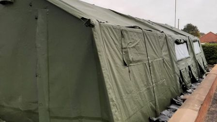 A green military-style tent is helping a suburban health centre with its life-saving Covid booster programme