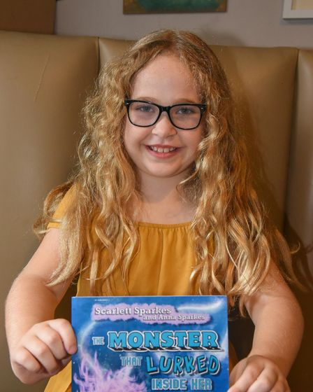 8-year-old Scarlett Sparkes with the book she has written titled The Monster That Lurked Inside Her