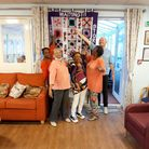 Nolly Mignol Gregory withher fellow Sparko friends and her community quilt.