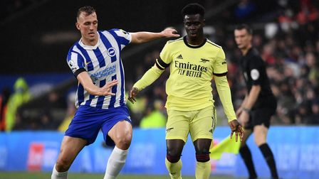 Brighton and Hove Albion's Dan Burn (left) and Arsenal's Bukayo Saka battle for the ball during the