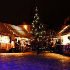 A Christmas tree is surrounded by brightly stalls lighting up the dark cobble stones.