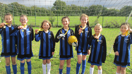 Radwinter Primary School show off their medals from their football tournament.