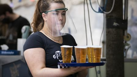A member of staff serves drinks in a beer garden at a UK pub as they start to reopen