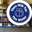 Clothes on shelves at Uttlesford Children's Clothing Bank, campaign logo words There With You This Winter